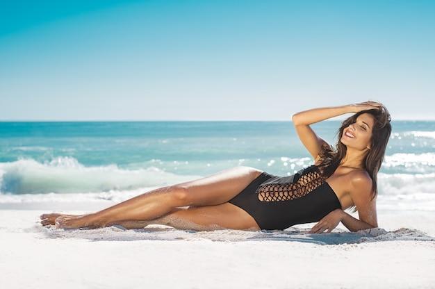 砂の上に横たわる笑顔の女性