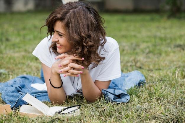 Улыбка женщины, лежащей на летней траве Бесплатные Фотографии