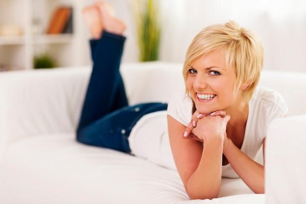 Donna sorridente sdraiata sul divano nel soggiorno