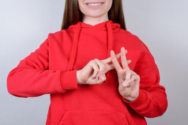 笑顔の女性が指を分離してハッシュタグサイン