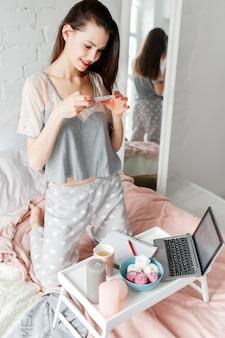笑顔の女性がスマートフォンで職場の朝の写真を撮ります。