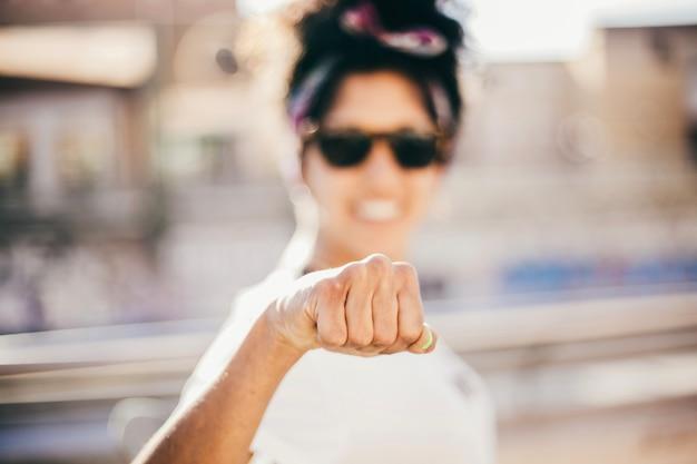 カメラで握った拳を作る笑顔の女性