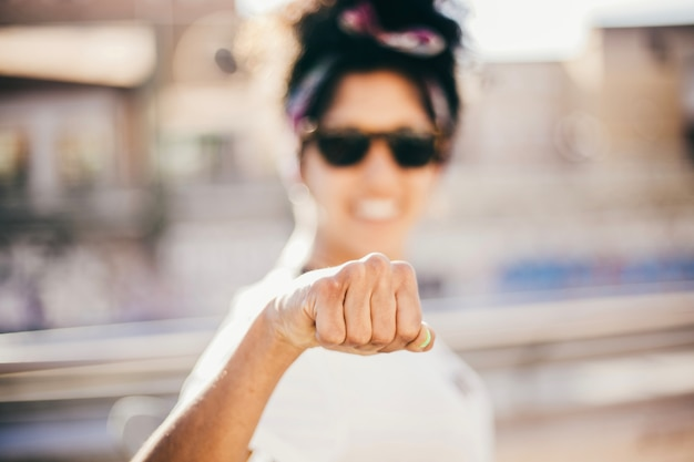 Smiling woman making clenched fist at camera