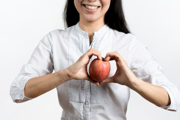 Smiling woman making heart shape with apple over white backdrop
