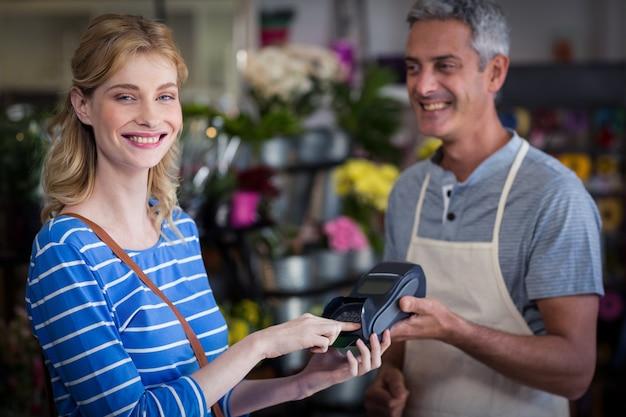 꽃집에 그녀의 신용 카드로 지불을 만드는 웃는 여자