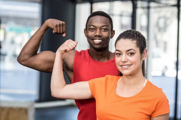 Smiling woman and man contracting biceps at crossfit gym