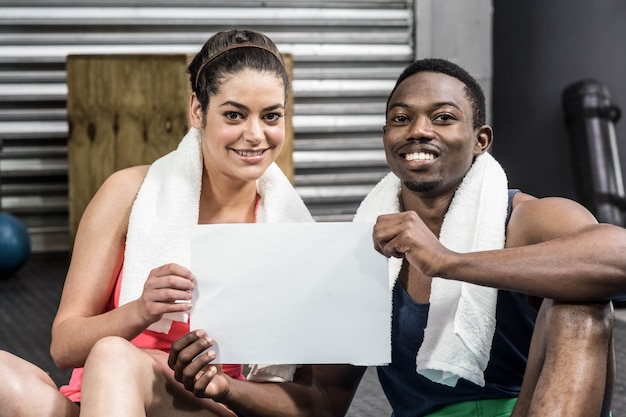 Smiling woman and man holding piece of paper at crossfit gym