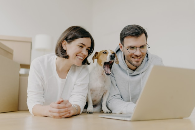 Smiling woman and man work on modern laptop computer, dog yawns, buy furniture for new apartment, lie on floor in spacious light room, have glad expressions. housewarming and repair concept