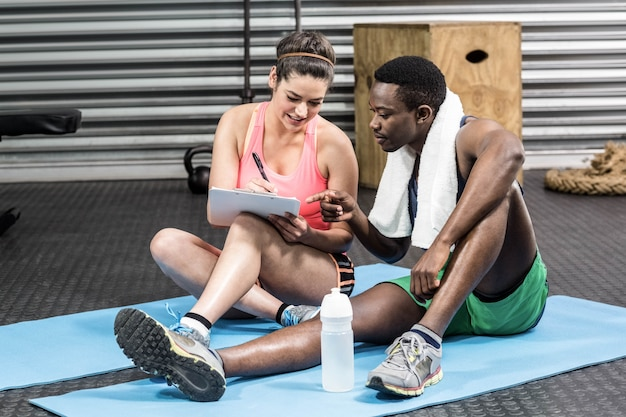 Smiling woman and man writing on paper at gym