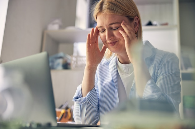 Smiling woman massaging her temples with closed eyes while keeping elbows on table