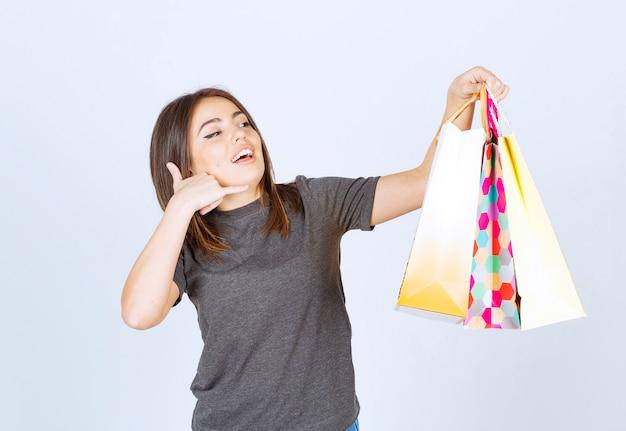 Una modella sorridente che porta un sacco di borse della spesa e fa un gesto di telefonata.