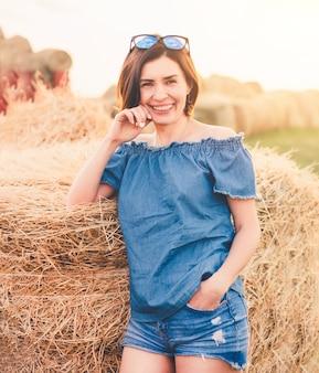 晴れた日に田舎で屋外干し草の山の近くの笑顔の女性 Premium写真