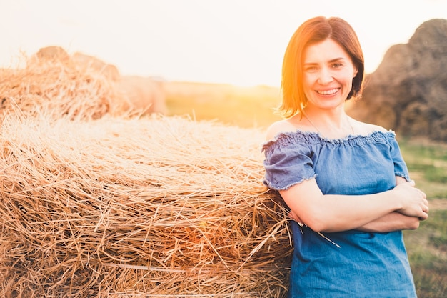 田舎の屋外干し草の山の近くの笑顔の女性