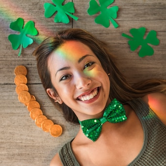 Smiling woman near heap of coins and paper clovers on floor