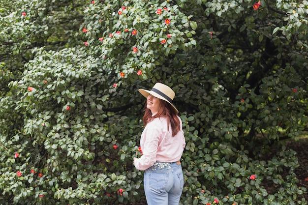 緑の小枝に成長している多くの花の近くに笑顔の女性