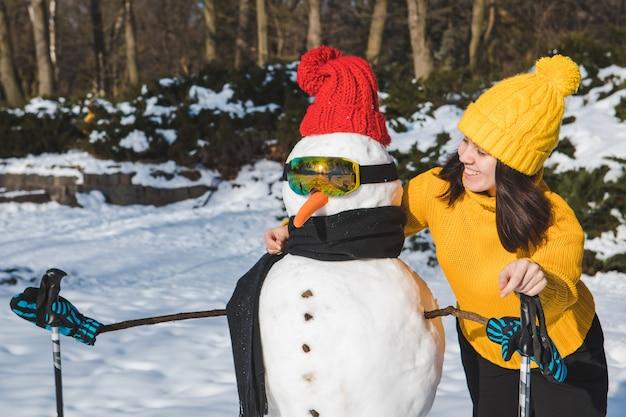 Улыбающаяся женщина возле лыжника, снеговика, копия пространства