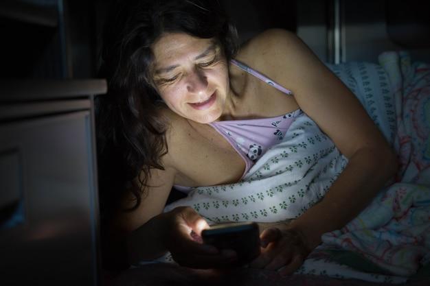 Улыбающаяся женщина ночное чтение в постели свет мобильного устройства