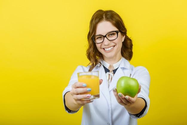 Улыбающаяся женщина-диетолог держит стакан апельсинового сока и яблоко, крупным планом