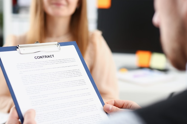 Smiling woman offer contract form on clipboard pad and silver pen to sign