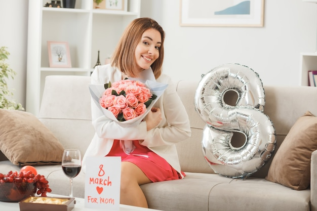 リビングルームのソファに座って花束を保持している幸せな女性の日に笑顔の女性