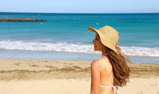 Улыбающаяся женщина на пляже вид сзади
