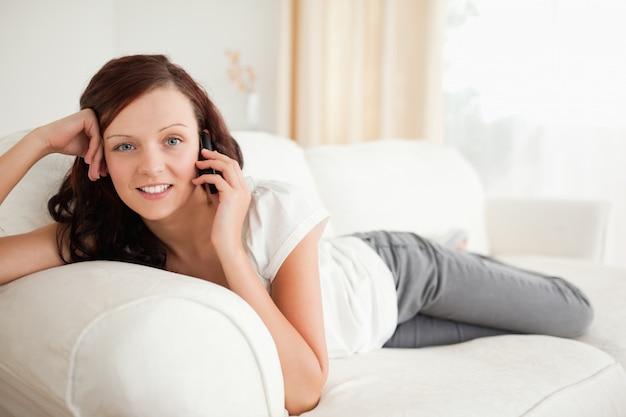 소파에 누워 전화에 웃는 여자