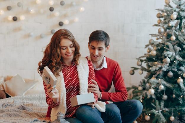 Улыбающаяся женщина открывает рождественский подарок