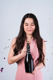 Smiling woman opening bottle of champagne