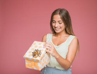 Smiling woman opening floral gift box with golden bow against colored backdrop