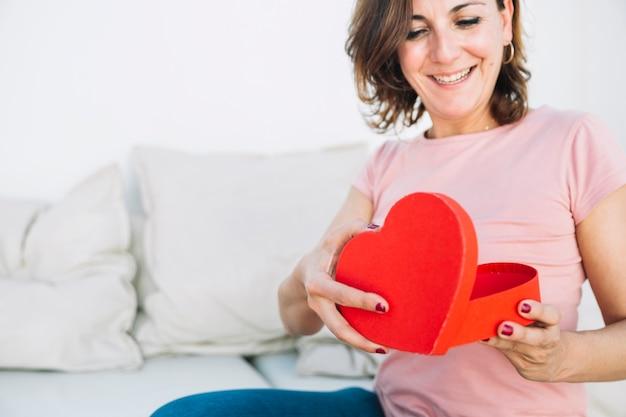 Улыбающаяся женщина, открывая коробку в форме сердца