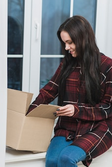 Smiling woman opening parcel