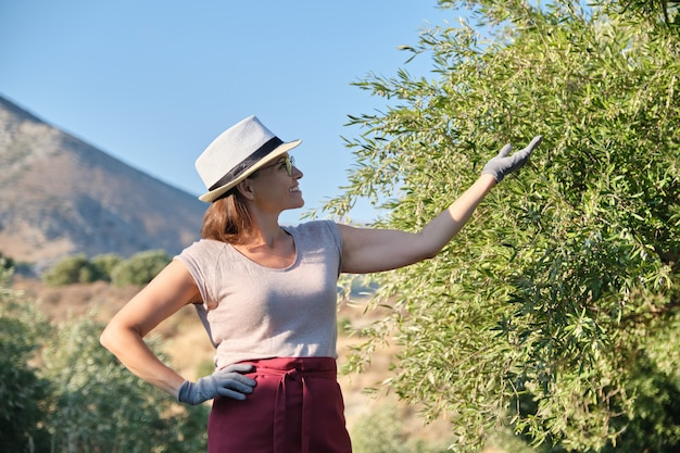 Smiling woman owner of an olive garden pointing to an tree