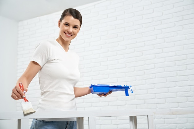 Smiling woman painting wooden rack