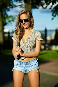 Smiling woman in the park in jean shorts