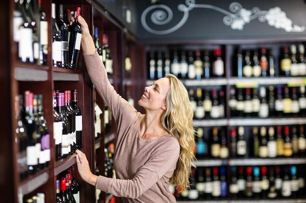 Улыбающаяся женщина, выбирая бутылку вина