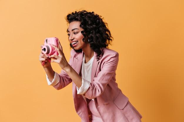 Donna sorridente in giacca rosa a scattare foto