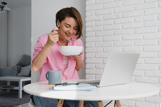Smiling woman in pink shirt having breakfast at home at table working online on laptop from home