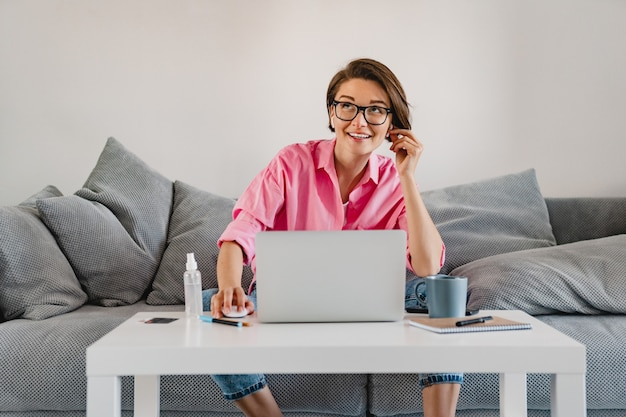 Smiling woman in pink shirt sitting relaxed on sofa at home at table working online on laptop from home