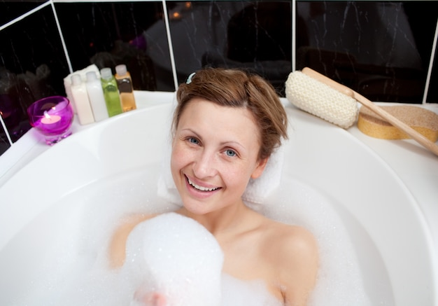 Smiling woman playing in a bubble bath