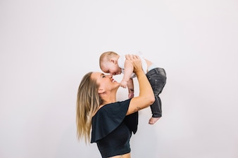 Smiling woman playing with baby