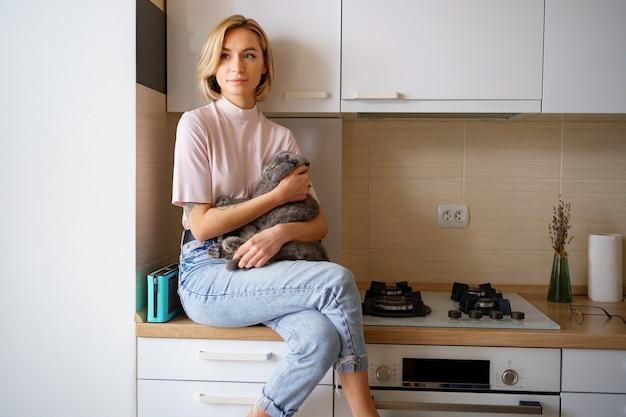 自宅のキッチンで猫と遊ぶ笑顔の女性。
