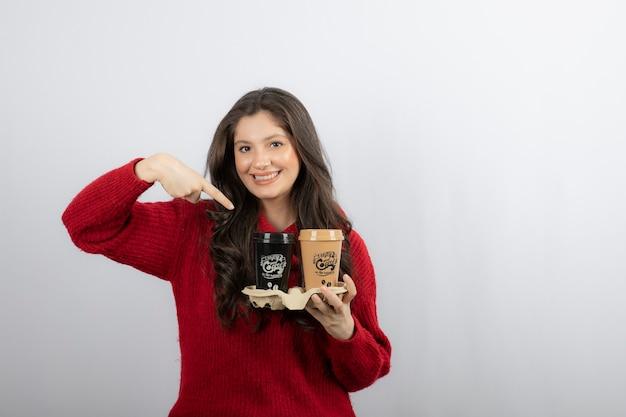 판지 홀더에 커피 컵을 가리키는 웃는 여자.