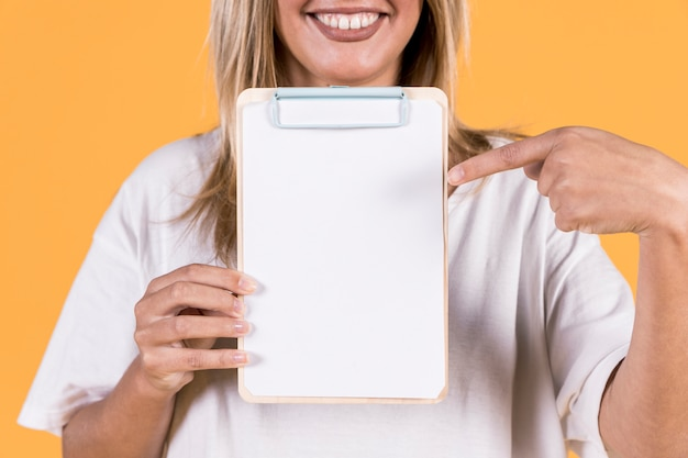 Smiling woman pointing finger at blank white paper on clipboard