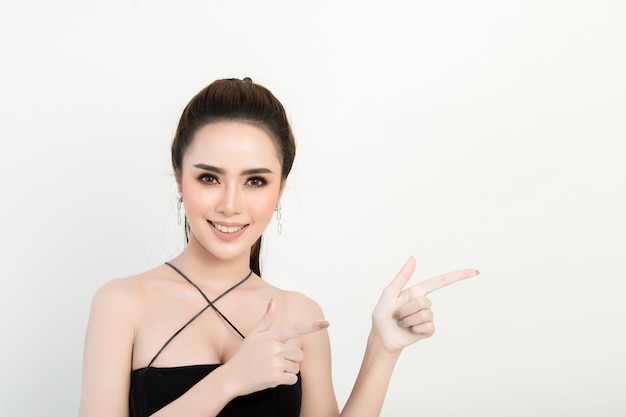 Smiling woman pointing finger side. isolated portrait on white