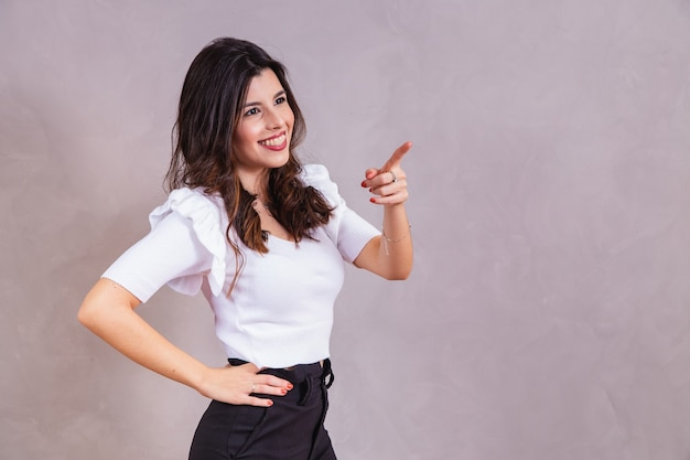 Smiling woman pointing her finger diagonally with free space for text.