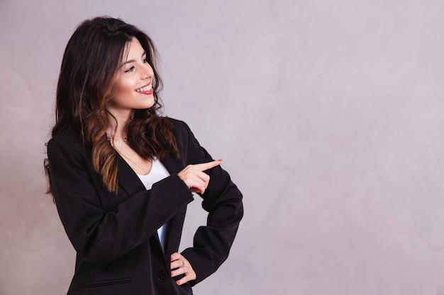 Smiling woman pointing to the side with free space for text.