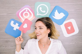 Smiling woman pointing upward in front of wall with social networking icons