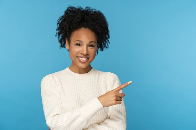 Smiling woman pointing with finger showing blank copy space