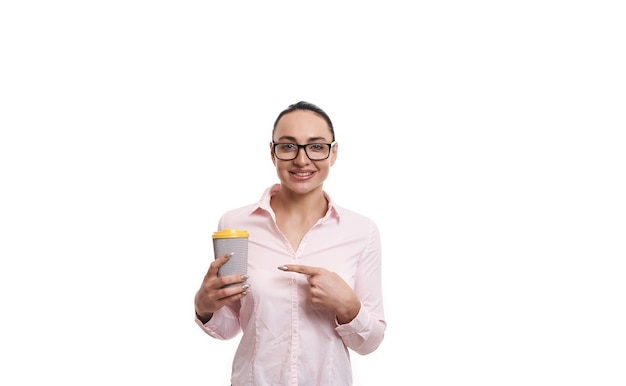 Smiling woman pointing with index finger at recyclable takeaway paper cup with hot drink isolated on white background with copy space