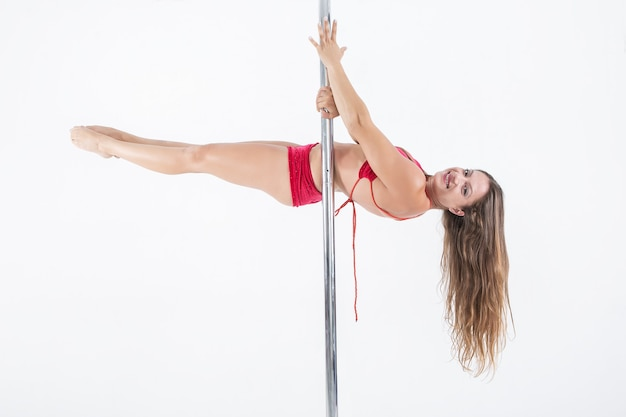 Smiling woman pole dancing on white background